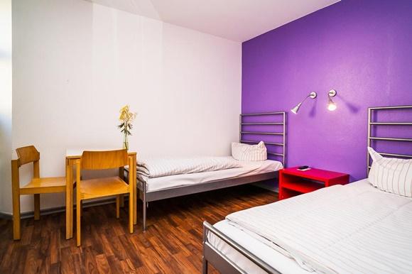 Mesinha lateral em frente às camas separadas por uma mesa de cabeceira Blog Vem Por Aqui