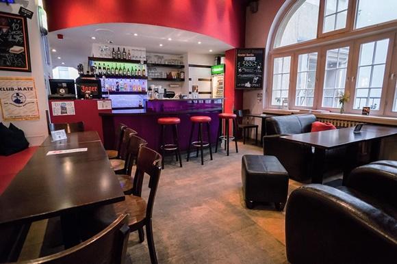 Bar do hostel com mesas e cadeiras de madeira escura e parede ao fundo pintada de vermelha Blog Vem Por Aqui