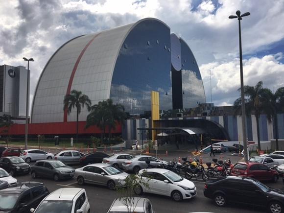 Prédio do shopping todo espelhado e com formato arredondado visto de fora com carros parados na frente Blog Vem Por Aqui