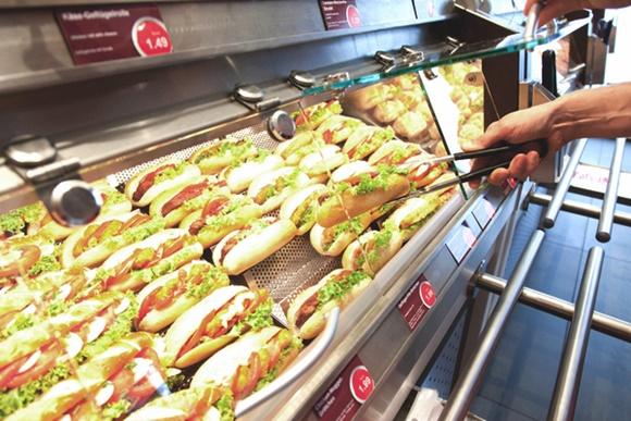 Mão segurando pegador e pegando sanduíche numa vitrine com várias unidades Blog Vem Por Aqui