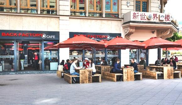 Loja da padaria com mesas de bancos de madeira à frente com toldos vermelhos Blog Vem Por Aqui
