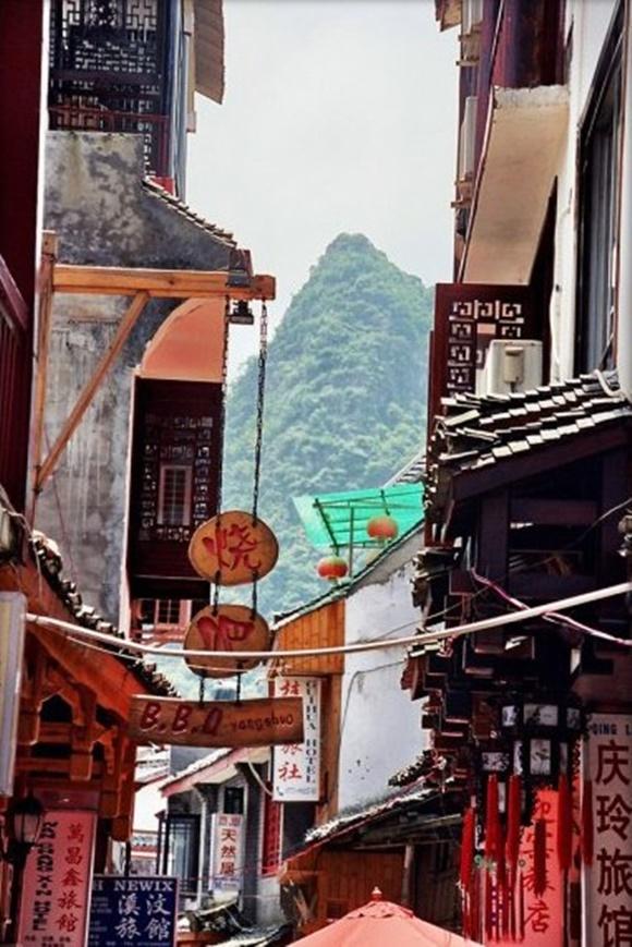 Centro da cidade com construções amontoadas dos dois lados de uma rua estreia, placas de madeira no alto e montanhas ao fundo Blog Vem Por Aqui