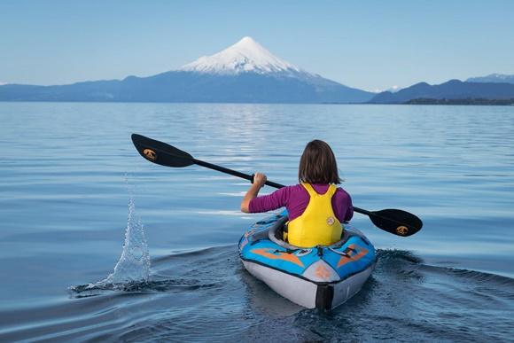 Mulher de costas, sentada num caiaque, dentro do lago, de frente ao vulcão Blog Vem Por Aqui