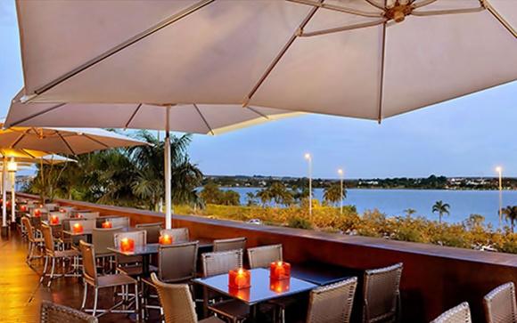Varanda do Coco Bambú com mesas no canto e vista para o lago Blog Vem Por Aqui