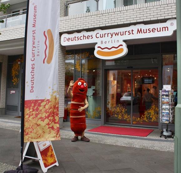 Fachada do museu com letreiro e homem vestido de salsicha na frente Blog Vem Por Aqui