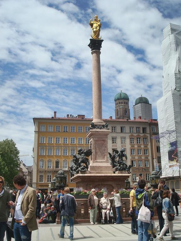 Monumento no meio da praça em mármore rosa com estátua dourada e pessoas circulando abaixo Blog Vem Por Aqui