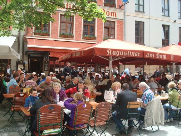 Bar com várias mesas no meio da praça, fachada pintada de vermelha e guarda-sóis da mesma cor Blog Vem Por Aqui