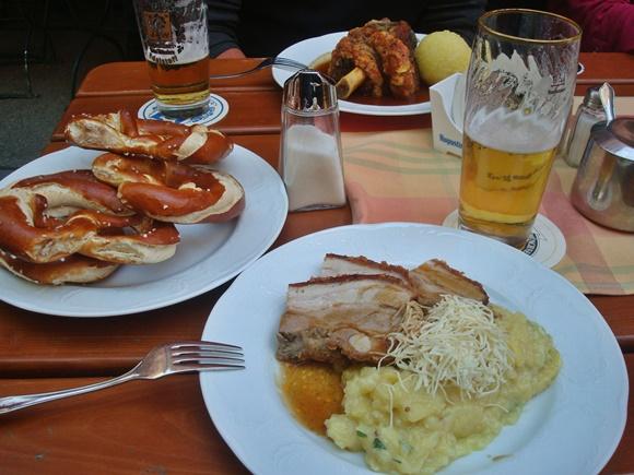 Mesa com prato de porco com purê, prato cheio de pretzels, cerveja, saleiro e prato com joelho ao fundo Blog Vem Por Aqui
