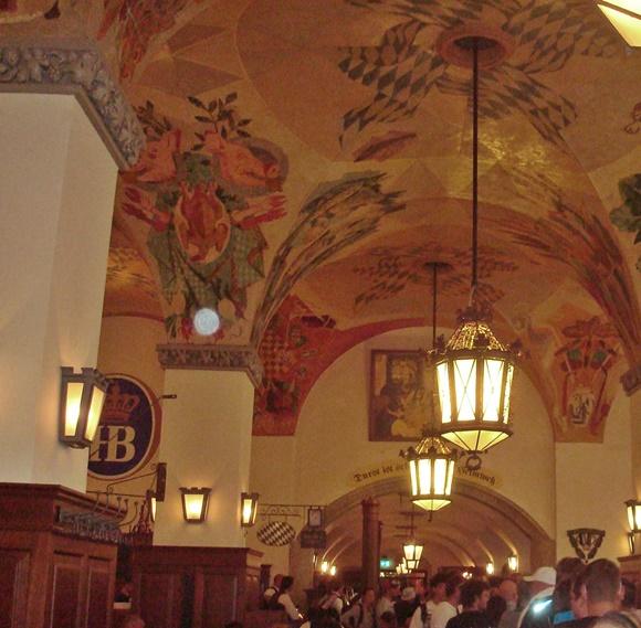 Interior da cervejaria com símbolo da marca nas paredes e teto pintado com desenhos verdes e rosas Blog Vem Por Aqui