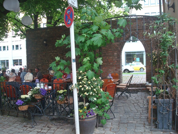 Parte externa do restaurante com plantas e árvores, uma cerca de metal, mesas, cadeiras e uma placa de sinalização na frente Blog Vem Por Aqui