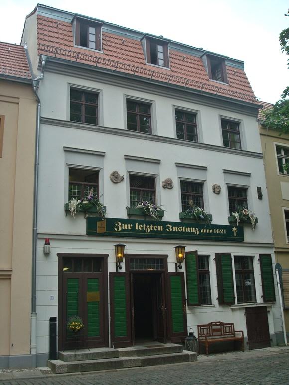 Fachada do restaurante com portas e janelas de madeira pintadas de verde e letreiro com o nome Blog Vem Por Aqui