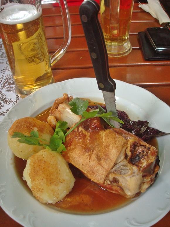 Prato com joelho de porco, bolinhas de batata amassada e faca cravada no meio, na frente uma caneca de cerveja Blog Vem Por Aqui