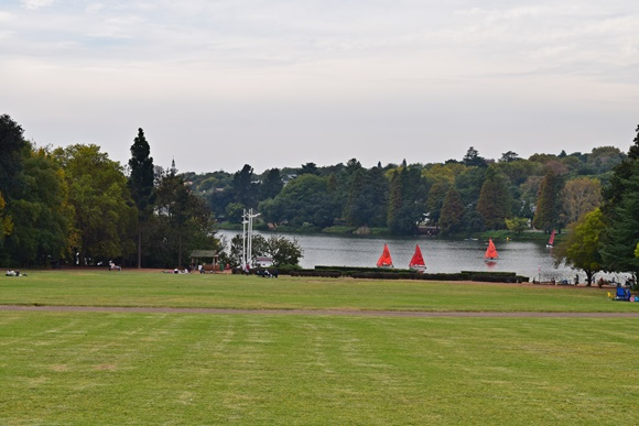 Longo gramado do Jardim com barquinhos ao fundo do lago rodeado por árvores Blog Vem Por Aqui