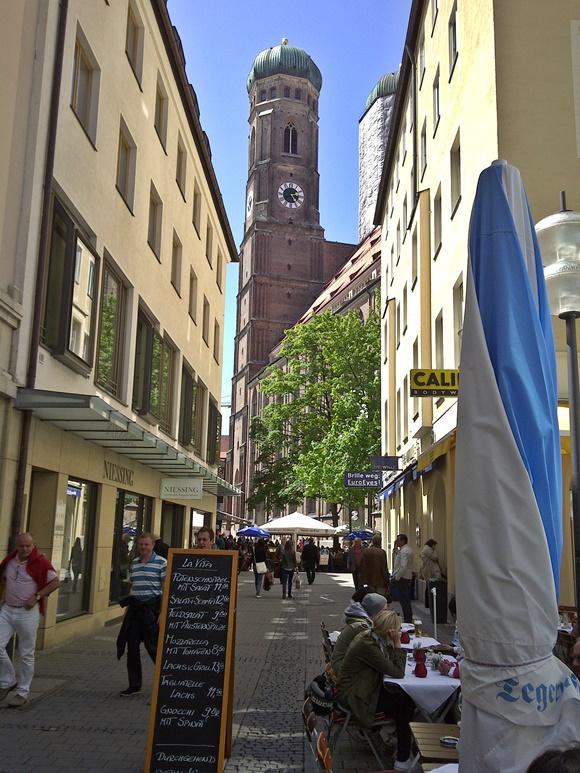 Torre no final da rua com lojas e placas de comércios Blog Vem Por Aqui