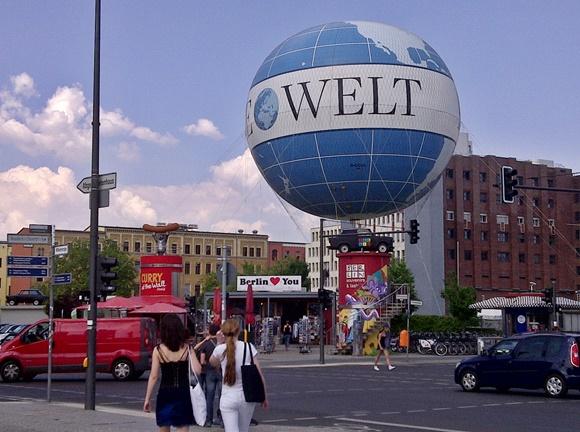 Mulheres passando de costas na rua e, do outro lado, um balão azul enorme escrito Welt Blog Vem Por Aqui