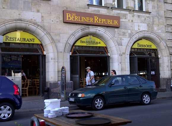 Fachada do bar com letreiro com o nome em cima dos arcos das portas de entrada com carros parados na porta Blog Vem Por Aqui