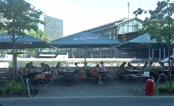 Mesinhas do bar com grande guarda-sol com o nome do estabelecimento na margem do rio com prédios ao fundo Blog Vem Por Aqui