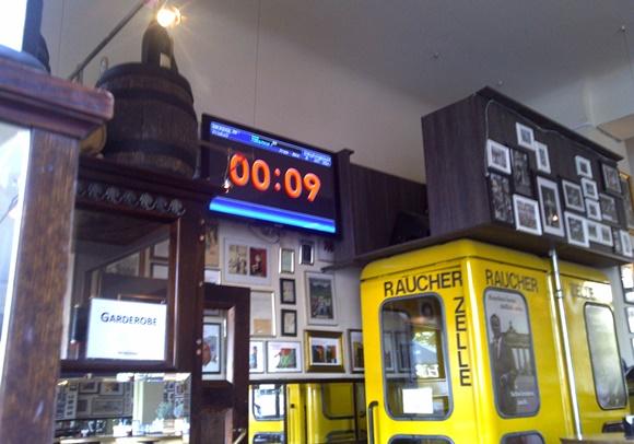Relógio digital aparecendo numa TV no alto do bar marcando 9 segundos Blog Vem Por Aqui
