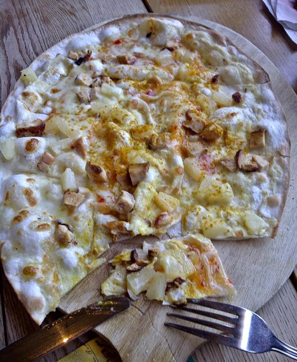Prato tipo pizza em cima de uma tábua de madeira com um garfo e uma faca na ponta da tábua Blog Vem Por Aqui