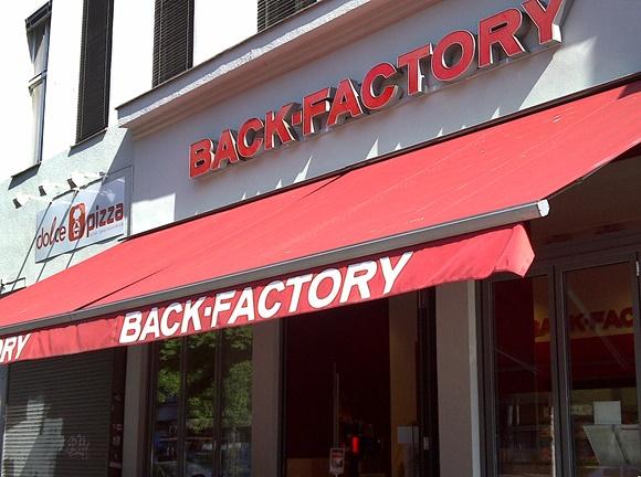 Letreiro da padaria em vermelho com toldo vermelho abaixo e nome escrito novamente, mas em branco Blog Vem Por Aqui