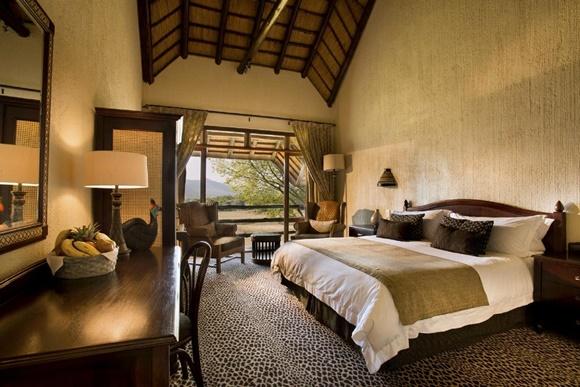 Quarto do lodge com cama larga e mesa de madeira com espelho na frente, varanda ao lado Blog Vem Por Aqui