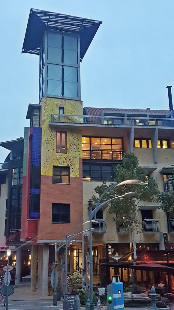 Torre de prédio pintada de amarelo do meio para cima e com tijolos aparentes embaixo. No alto, estrutura de vidro Blog Vem Por Aqui
