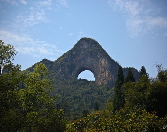 Montanha com formato triangular e buraco redondo no meio com árvores em volta e a frente e céu azul Blog Vem Por Aqui