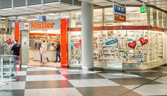 Fachada da loja da Muller no aeroporto com paredes de vidro e letreiro no nome e símbolo da loja Blog Vem Por Aqui