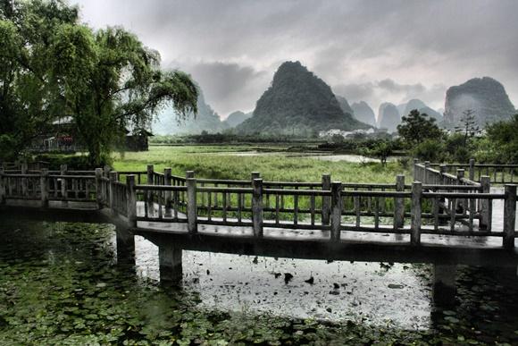Ponte pequena de madeira sobre rio com montanhas ao fundo e céu nublado Blog Vem Por Aqui