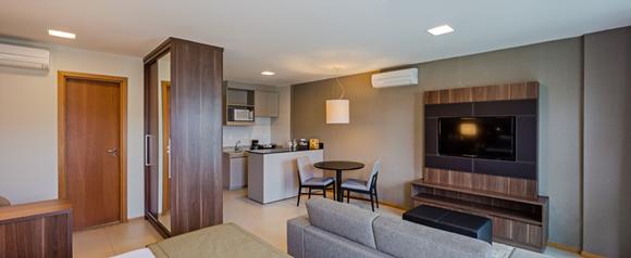Sala do apartamento com cozinha no canto, mesa à frente, sofá diante da TV Blog Vem Por Aqui