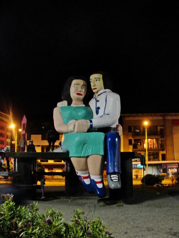 Estátua de um casal em tamanho gigante sentados num banco. A mulher está de vestido verde e pernas cruzadas abaixo do joelho, meias brancas e sapatos azuis, o home está de camisa branca e calça azul e ela está sentada no colo dele, por isso só se vê uma perna com sapato cinza Blog Vem Por Aqui