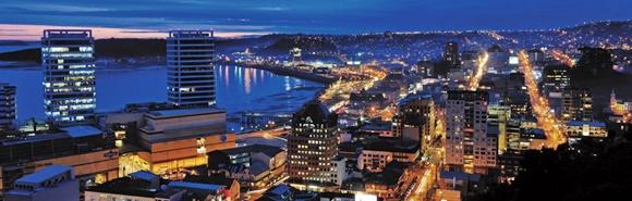 Vista noturna de Puerto Montt com prédios iluminados e lago Blog Vem Por Aqui