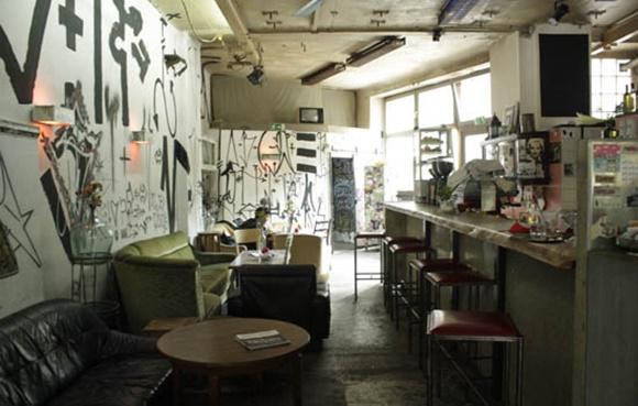 Interior do bar com paredes todas pichadas, balcão e sofás velhos diante de mesinhas Blog Vem Por Aqui