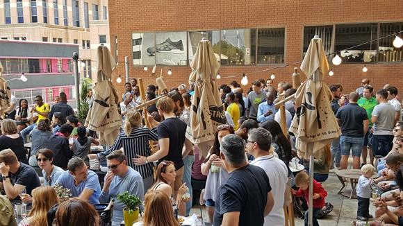 Terraço do prédio cheio de pessoas em pé conversando Blog Vem Por Aqui