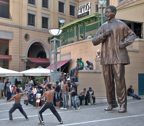 Estátua gigante de Nelson Mandela e meninos sem camisa, de calça preta, dançando na frente e pessoas observando Blog Vem Por Aqui