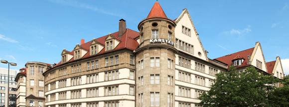 Fachada de uma das lojas da marca prédio antigo de telhado vermelho com letreiro no topo da torre principal Blog Vem Por Aqui