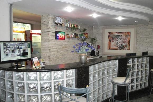 Bar com tijolos de vidro e cadeiras brancas, quadro antigo e flor artificial Blog Vem Por Aqui