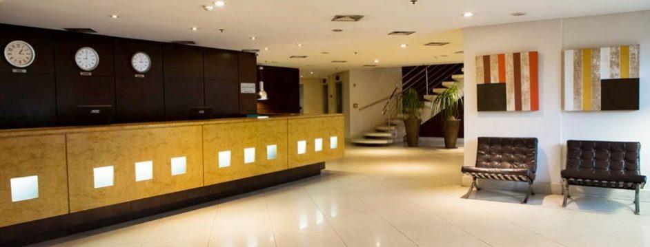 Lobby do Victory Business, com balcão bege com pontos iluminados no meio, parede preta e poltronas pretas em frente Blog Vem Por Aqui