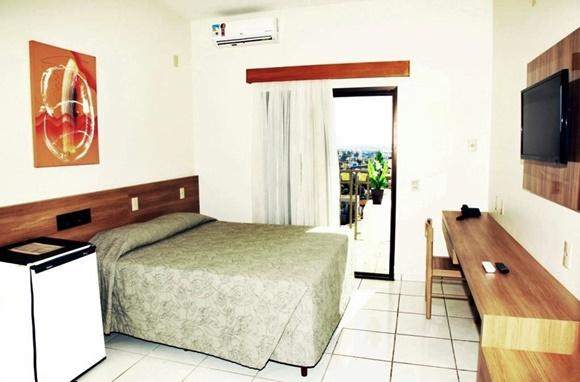 Quarto com frigobar do lado da cama, que está diante de um painel de madeira e tem colcha verde e um quadro vermelho acima Blog Vem Por Aqui