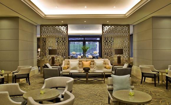 Lobby do hotel com mesas e poltronas individuais, sofá grande com mesa de centro e, ao fundo divisórias Blog Vem Por Aqui