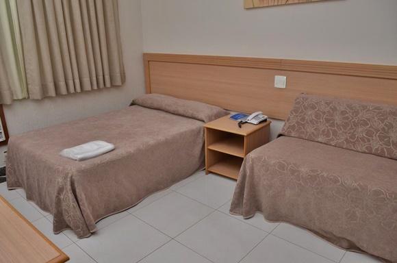 Cama com colcha marrom, em frente a um painel de madeira, sofá-cama coberto com a mesma colcha Blog Vem Por Aqui