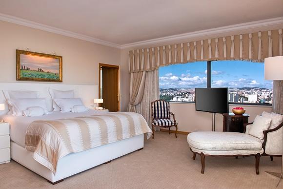 Quarto do hotel Dom Pedro, com janela ampla com vista para a cidade, cama larga e chaise longue em frente Blog Vem Por Aqui