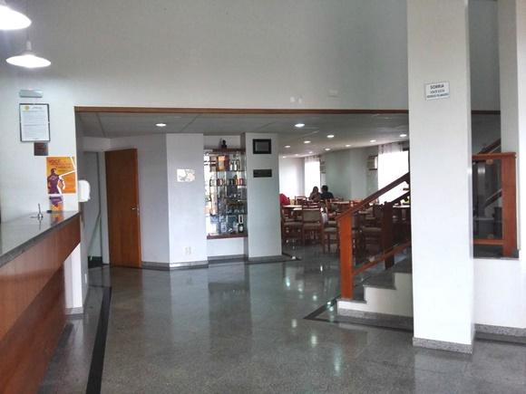 Lobby com recepção ao lado esquerdo, escada ao lado direito e restaurante ao fundo Blog Vem Por Aqui