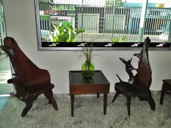 Lobby com cadeiras de madeira, janela e, ao fundo, as grades Blog Vem Por Aqui