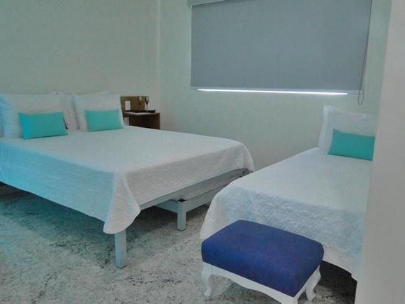 Camas com colchas brancas e almofadas verdes, em frente, banquinho azul Blog Vem Por Aqui