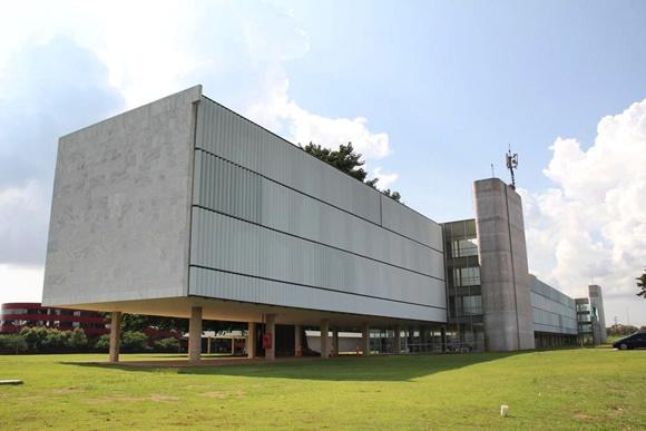 Foto de frente do prédio mostrando a extensão e gramado em volta Blog Vem Por Aqui