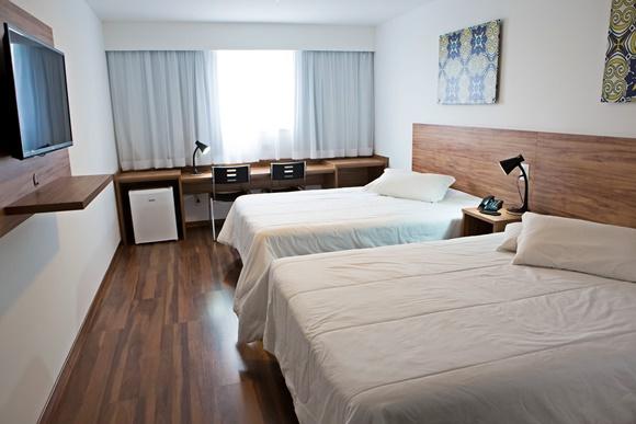 Quarto com duas camas e, no fim, mesa de madeira com duas cadeiras e frigobar embaixo. Na frente, painel com TV Blog Vem Por Aqui