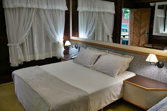 Cortina de babados branca, cama branca com espelho em cima e mesa de cabeceira de madeira com abajur Blog Vem Por Aqui