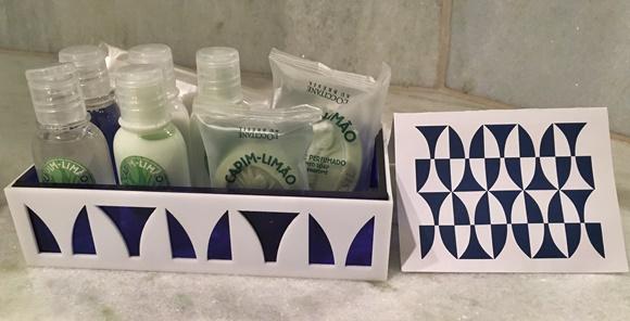 Estojo branco com parte azuis com pequenos vidros e sabonetes L'Occitane e, ao lado, cartão com a mesma arte do estojo Blog Vem Por Aqui