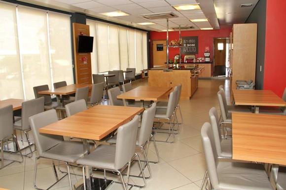 Restaurante do hotel com mesas de madeira e cadeira estofadas com courino bege Blog Vem Por Aqui